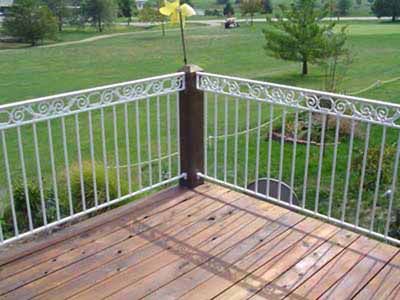 Powdercoated outdoor deck railing with scrollwork mouonted to wood posts