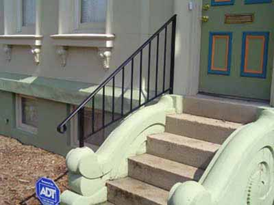 Decorative single stair rail mounted to concrete stairs
